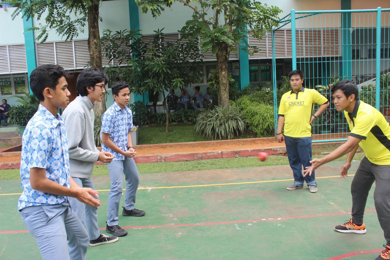 Pengurus Cricket Kota DEpok mengajarkan cara melempar bola kepada siswa