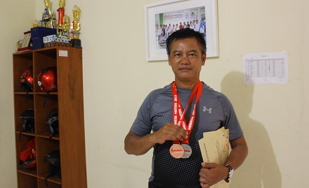 Deni Suprayogi dengan bangga memamerkan medali yang diraih