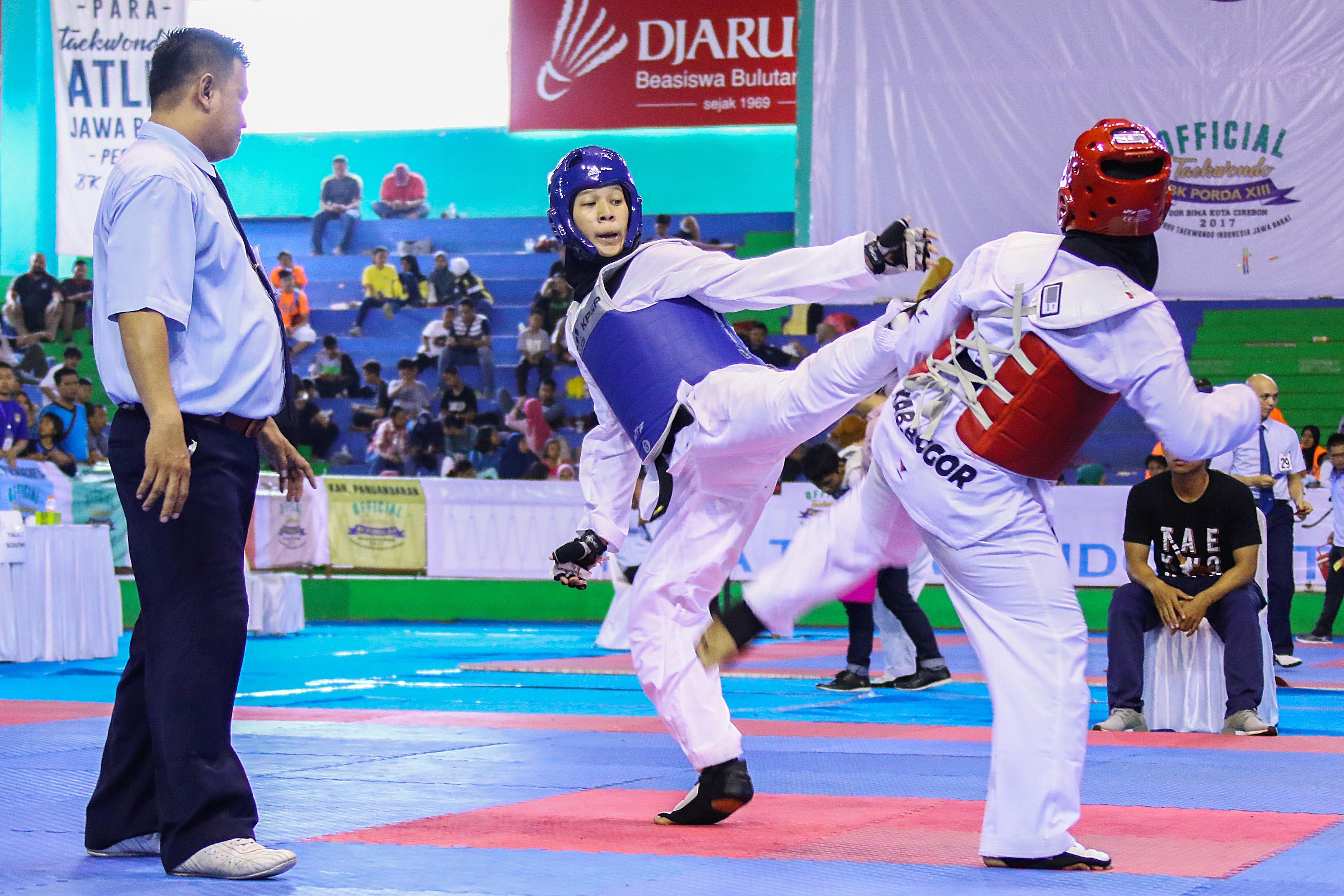 Ari Febrian (Sudut Biru), Taekwondoin Kota Depok saat sedang bertanding melawan Kab. Bogor di GOR Bima, Cirebon pada Minggu (15/10). Foto: Faruqi.