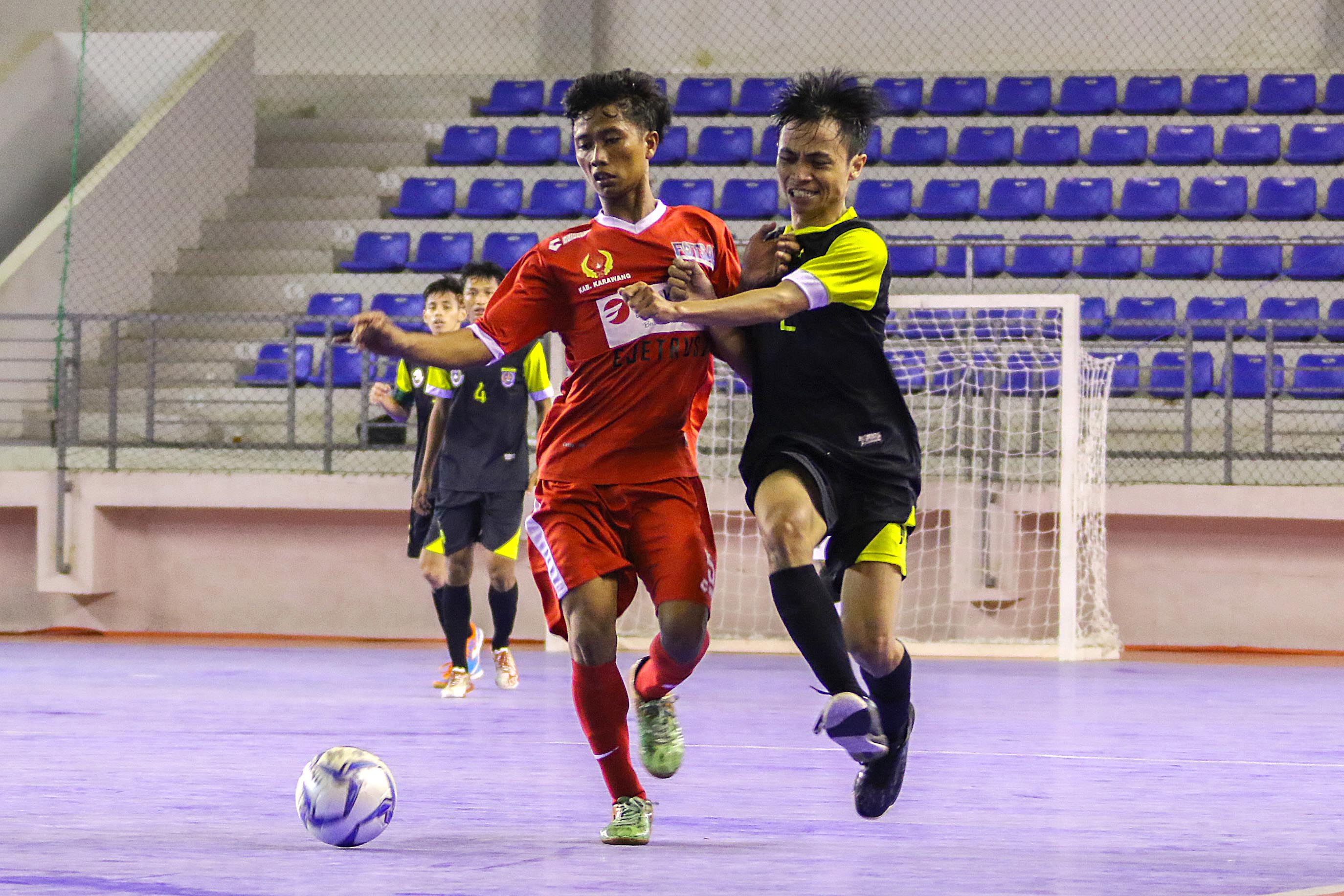 Pemain Depok (hitam-kuning) sedang berduel merebut bola dengan pemain Kab. Karawang (merah) pada laga kemarin (14/10).