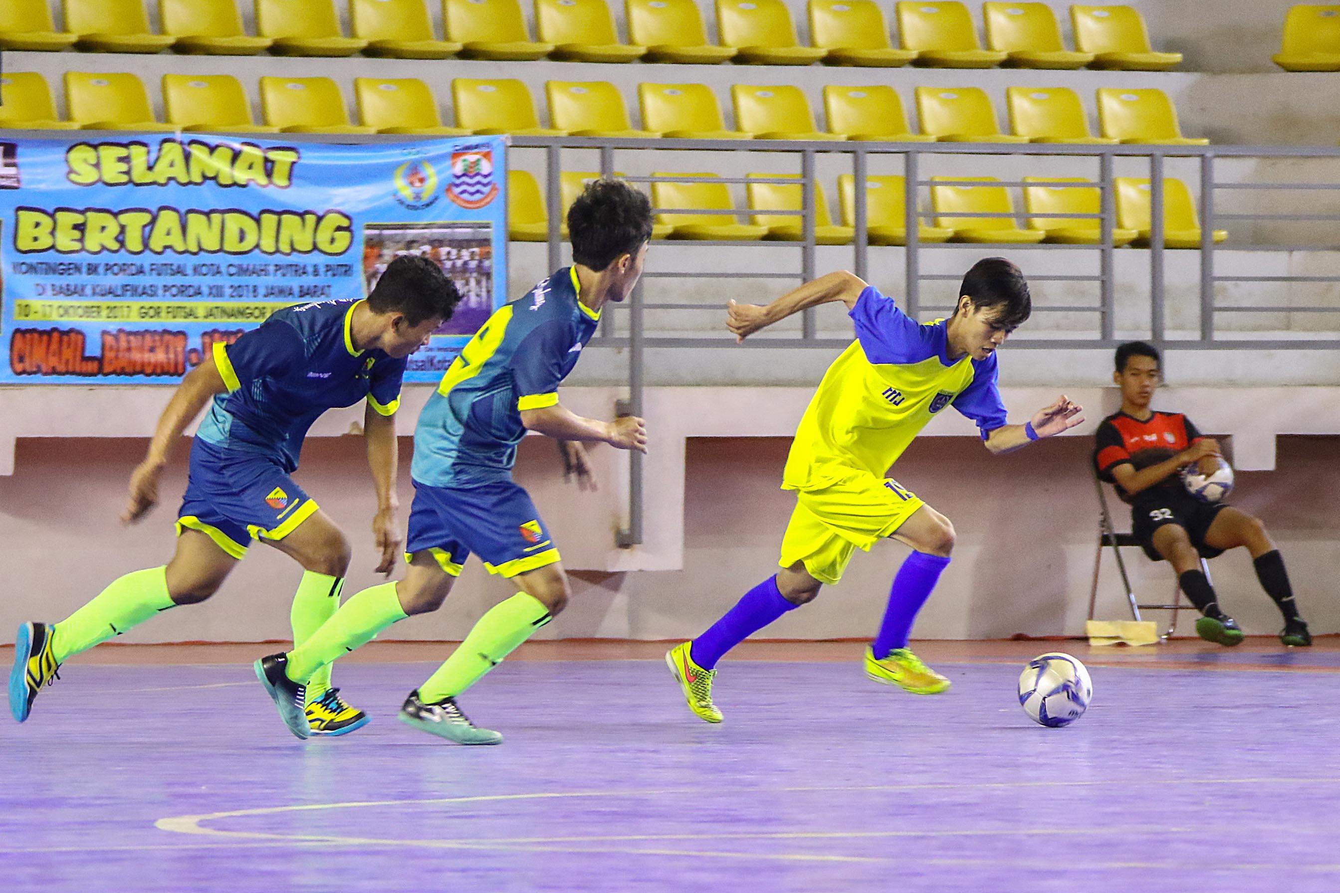Atlet Futsal Kota Depok (kuning) sedang berusaha melewati pemain Kab. Bandung (hijau, biru). Foto: Faruqi.