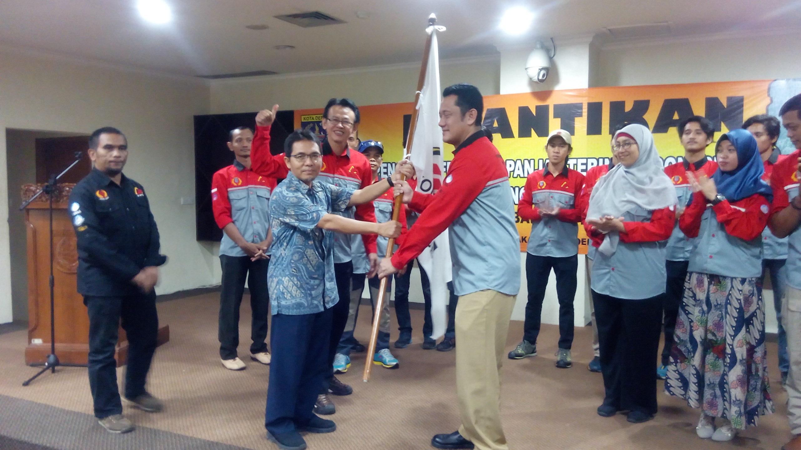 Ketua KONI Kota Depok Drs. Amri Yusra. M.Si. memberikan bendera FPTI kota Depok kepada Ketua FPTI Baru sebagai symbol resmi kepengurusan FPTI yang baru periode 2018-2023