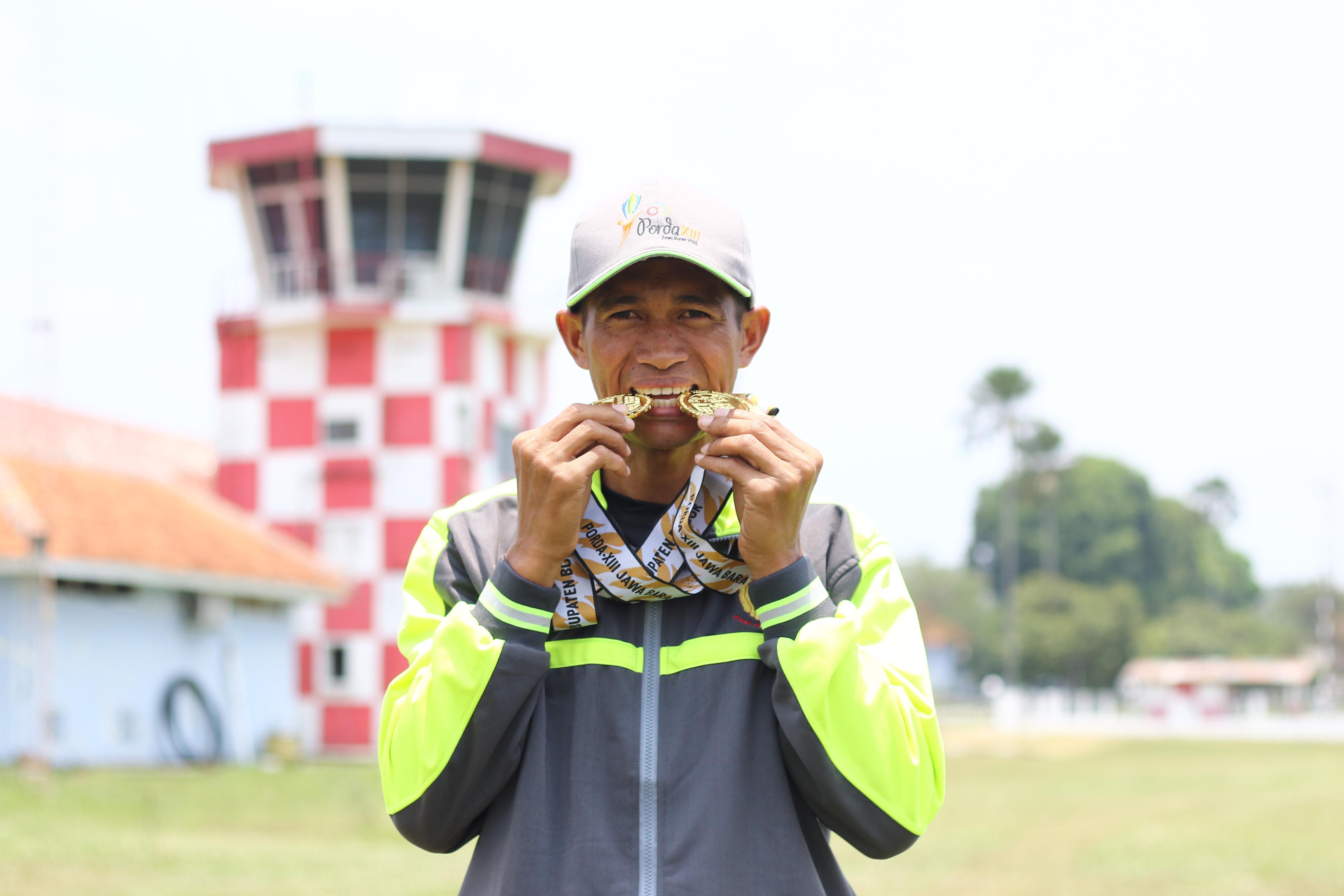 Arwis, Atlet Terjun Payung Kota Depok berpose dengan medali emas yang berhasil diraihnya pada PORDA JABAR XIII-2018 di Lanud. Atang Sendjaja, Semplak, Bogor pada Sabtu (29/9) siang. Arwis berhasil mempersembahkan dua medali emas untuk Kota Depok di nomor Ketepatan Mendarat Perorangan dan Beregu Putra. KONI KOTA DEPOK/Faruqi/2018