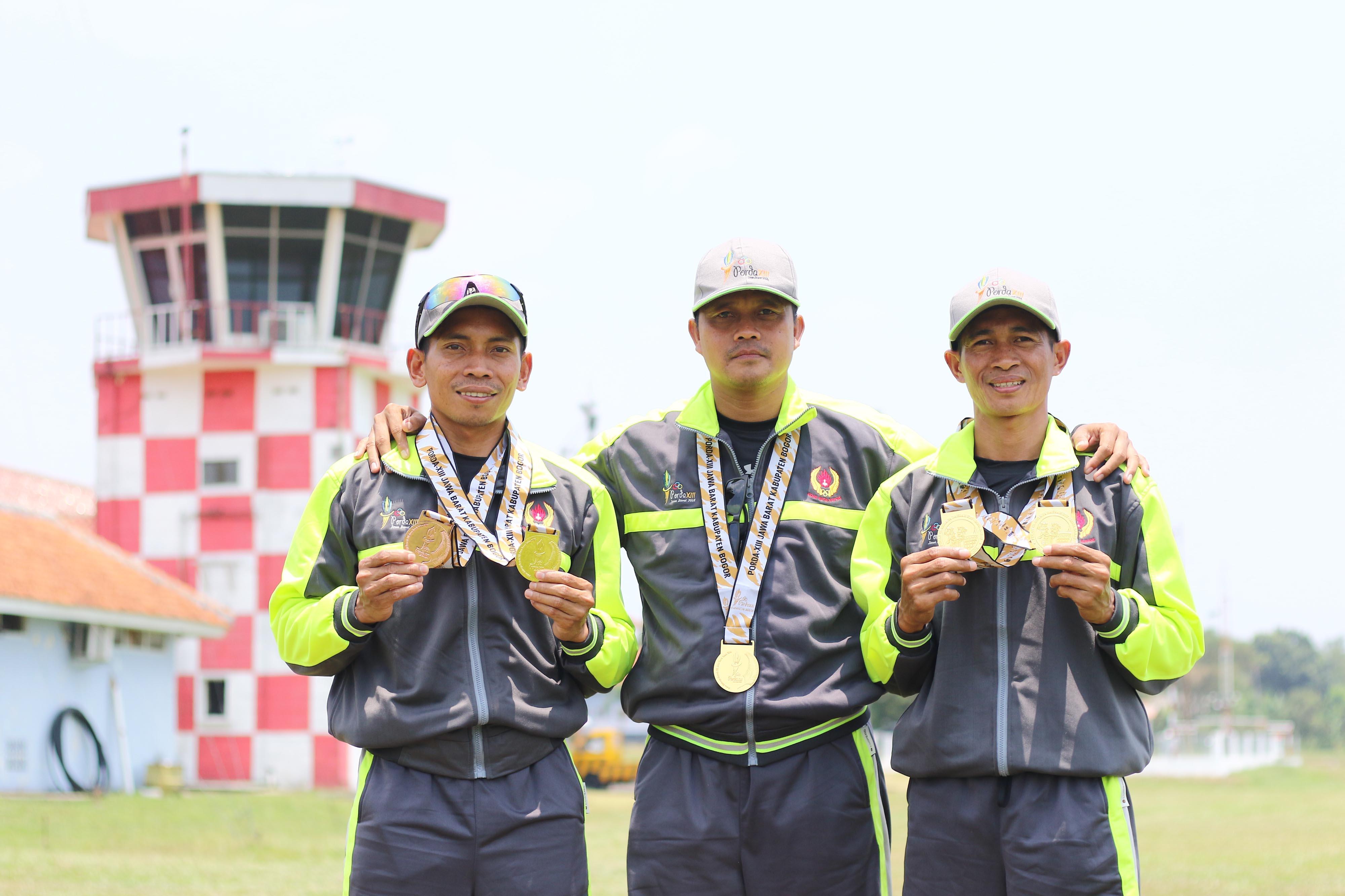 Atlet Terjun Payung Kota Depok, Arwis (kanan), Pepen (tengah) dan Ismail Doda (kiri) berpose bersama dengan medali emas yang berhasil mereka raih di nomor Ketepatan Beregu Putra PORDA JABAR XIII-2018 di Lanud. Atang Sendjaja, Semplak, Bogor pada Sabtu (29/9) siang. KONI KOTA DEPOK/Faruqi/2018