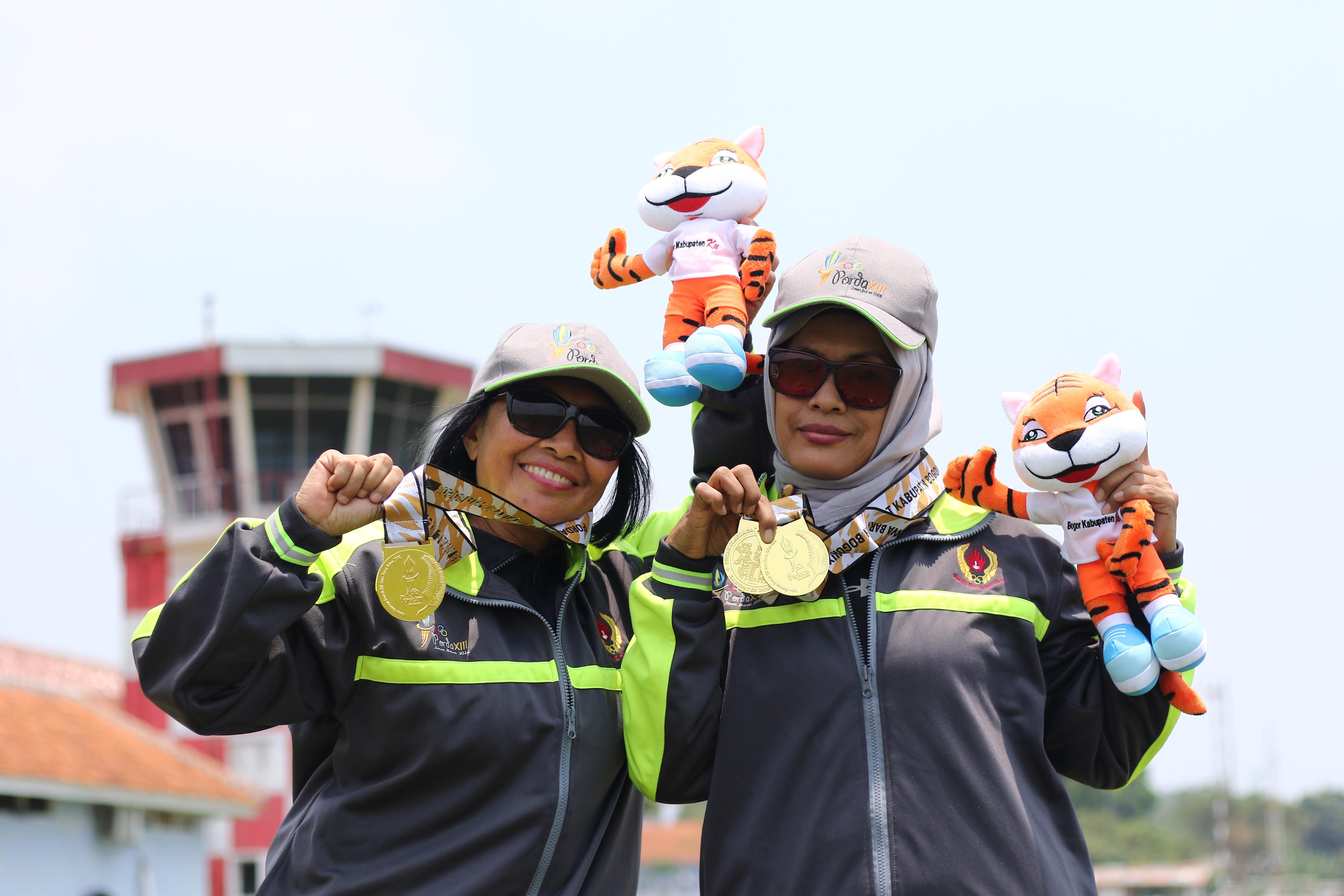 Atlet Terjun Payung Kota Depok, Tuti Lestari (kanan) dan Dede (kiri),berpose dengan medali emas yang berhasil mereka raih pada PORDA JABAR XIII-2018 di Lanud. Atang Sendjaja, Semplak, Bogor pada Sabtu (29/9) siang. Tuti berhasil mempersembahkan medali emas untuk Kota Depok di nomor Ketepatan Mendarat Perorangan dan Beregu Putri, sedangkan Dede meraih medali emas di nomor Ketepatan Mendarat Beregu Putri. KONI KOTA DEPOK/Faruqi/2018