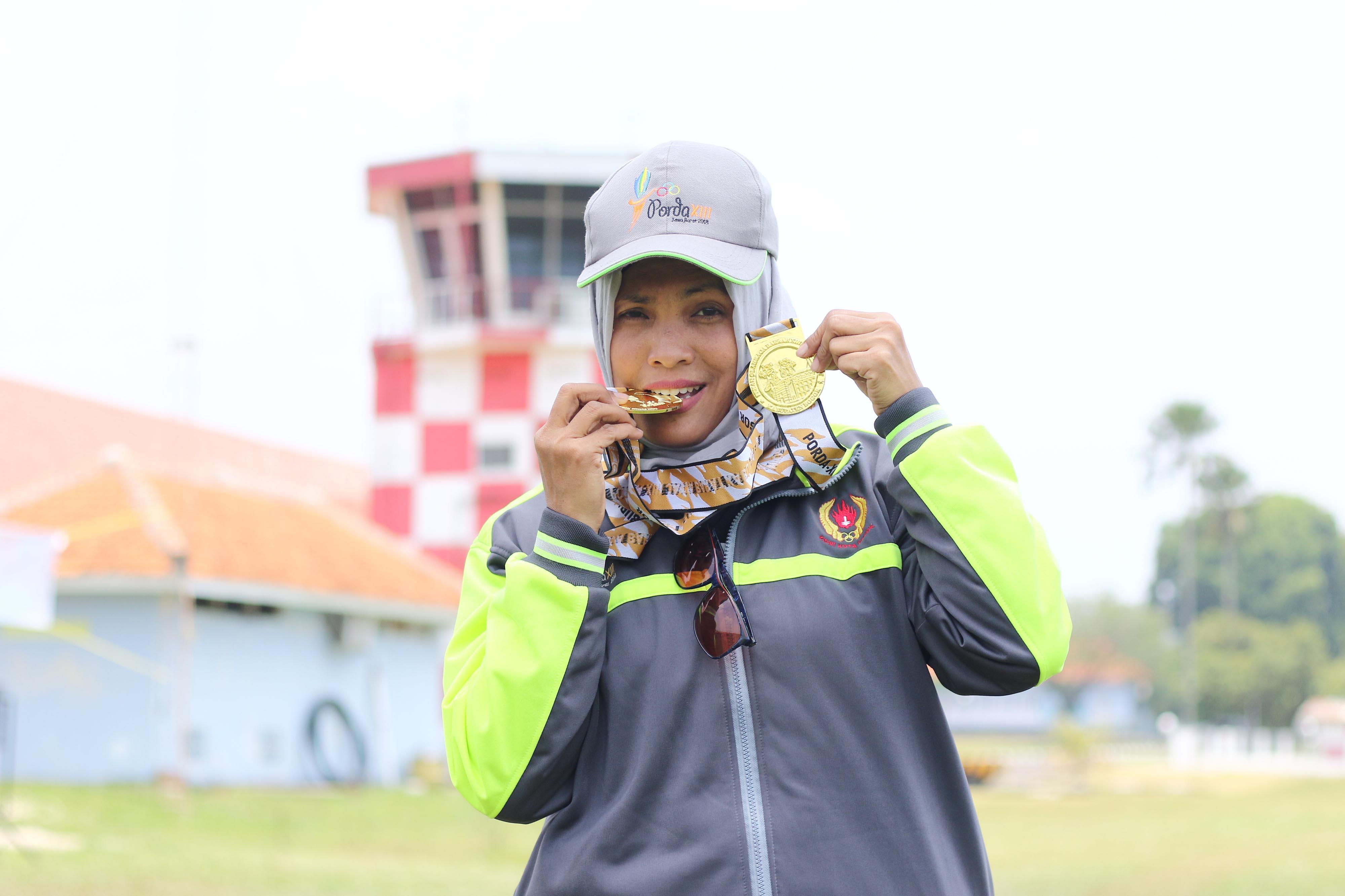 Tuti Lestari, Atlet Terjun Payung Kota Depok berpose dengan medali emas yang berhasil diraihnya pada PORDA JABAR XIII-2018 di Lanud. Atang Sendjaja, Semplak Bogor pada Sabtu (29/9) siang. Tuti berhasil mempersembahkan medali emas untuk Kota Depok di nomor Ketepatan Mendarat Perorangan dan Beregu Putri. KONI KOTA DEPOK/Faruqi/2018