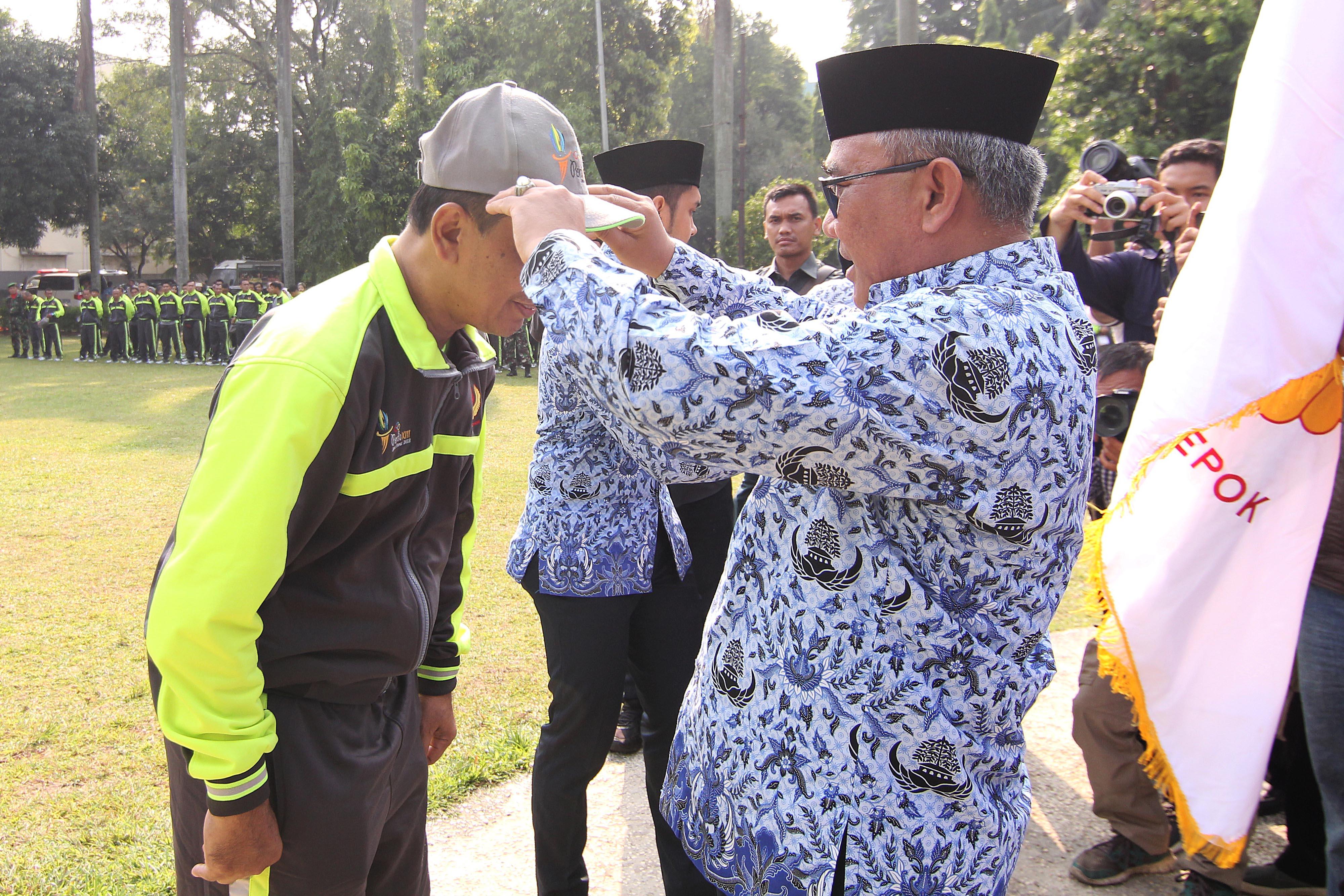 Mohammad Idris, Walikota Depok (kanan) memakaikan topi kepada Herry Suprianto, Ketua Kontingen Kota Depok PORDA Jabar XIII-2018 (kiri), sebagai tanda pelepasan kontingen oleh Walikota Depok di Balaikota Depok, Senin (1/10) pagi. KONI KOTA DEPOK/Faruqi/2018